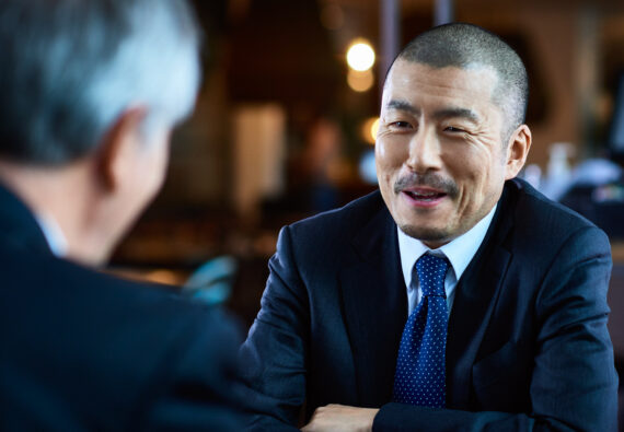 Japanese businessman sitting opposite male coworker in restaurant